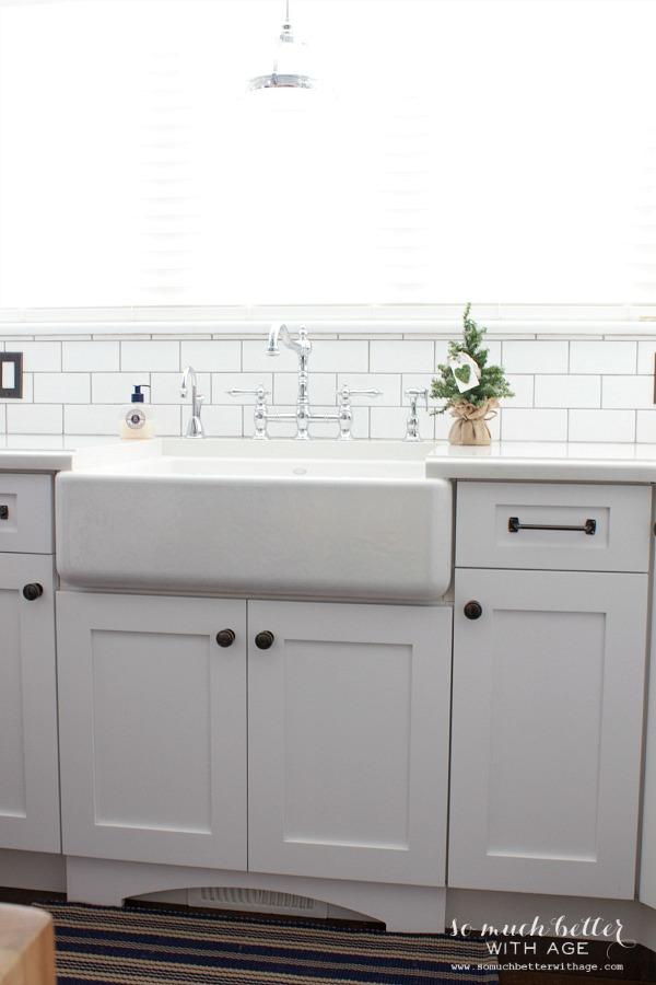 Farm sink in white kitchen   somuchbetterwithage.com